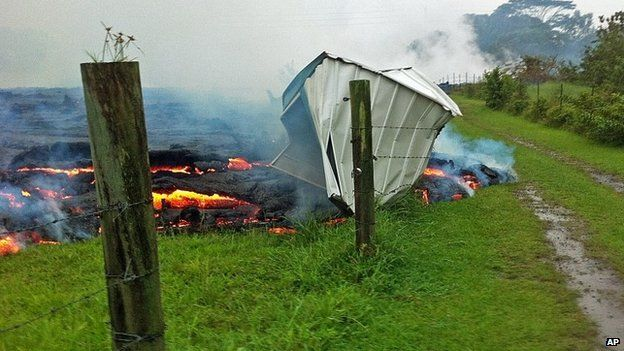 This Oct. 25, 2014 photo provided by the U.S. Geological Survey shows a small shed being consumed by lava in a pasture between the Pahoa cemetery and Apa?a Street near the town of Pahoa on the Big Island of Hawaii. Dozens of residents in this rural area of Hawaii were placed on alert as flowing lava continued to advance.