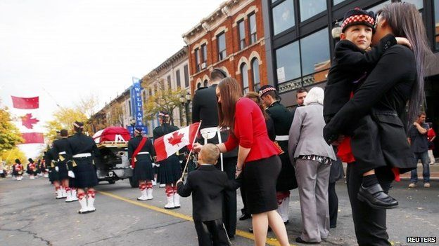Marcus Cirillo, 5, is carried by his aunt, Natasha Cirillo during the funeral procession for his father, Cpl. Nathan Cirillo in Hamilton, Ontario October 28, 2014.