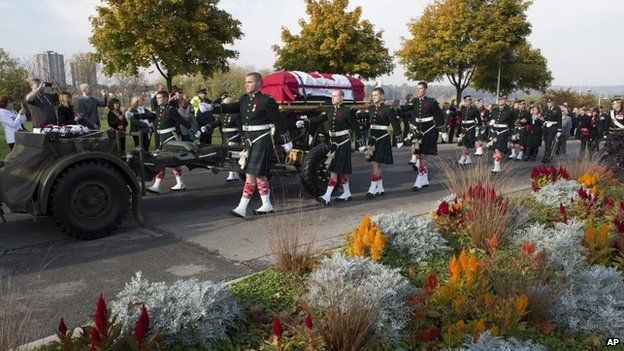 The coffin of Cpl Nathan Cirillo is towed on a gun carriage during his funeral procession in Hamilton, Ontario 28 October 2014