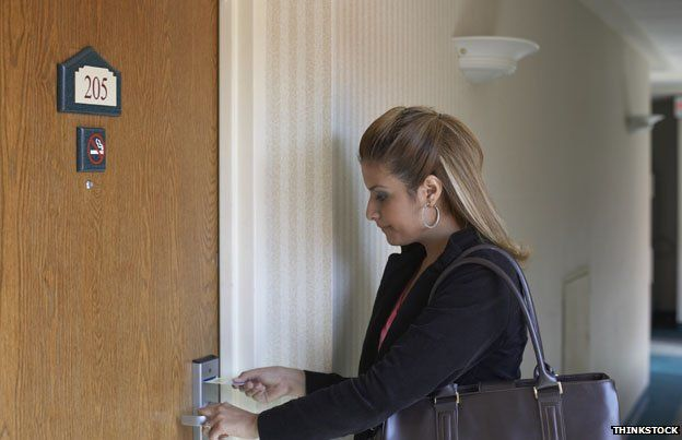 Woman opens hotel door with key card