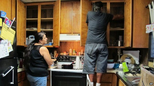 Denise Lagrimas, left, and her brother Beatle Rodriguez pack dishes at their home in Pahoa, Hawaii, on 28 October 2014