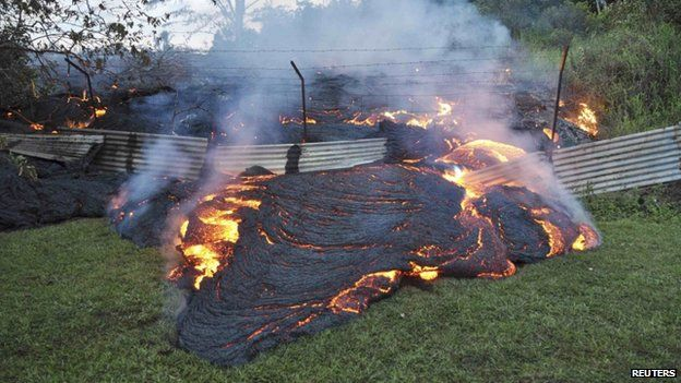 The lava flow from the Kilauea Volcano burned vegetation as it approaches a property boundary in Pahoa, Hawaii, on 28 October