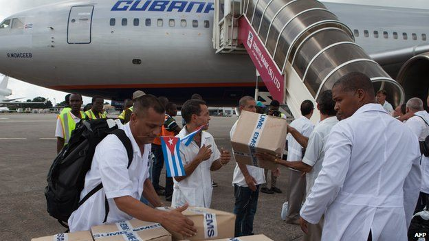 The first members of a team of 165 Cuban doctors and health workers upon their arrival at Freetown's airport to help the fight against Ebola in Sierra Leone, on October 2, 2014.