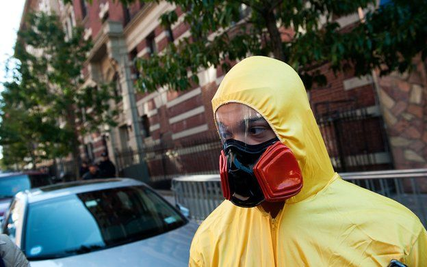 A man, dressed in a biohazard costume, stands on the corner of 546 West 147th Street in New York City