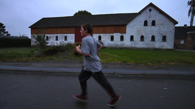 Mike running along a road with rural building in the background