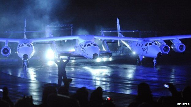 Virgin Galactic's SpaceShipTwo (C), which is carried by a twin-hulled aircraft named Eve, is unveiled in Mojave, California in this 7 December 2009