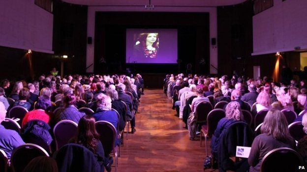 Images of Alice Gross are shown during a public memorial service
