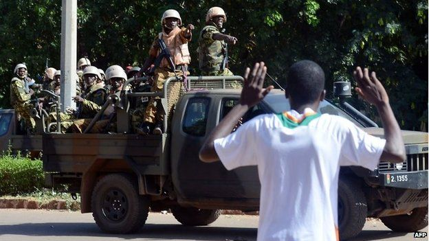A man gestures as Burkinese troops arrive to the national television headquarters after shots were fired around the premises in Ouagadougou, 2 November 2014