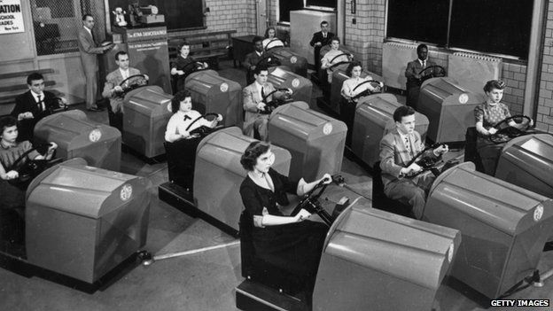1953 image of people learning to drive in simulators