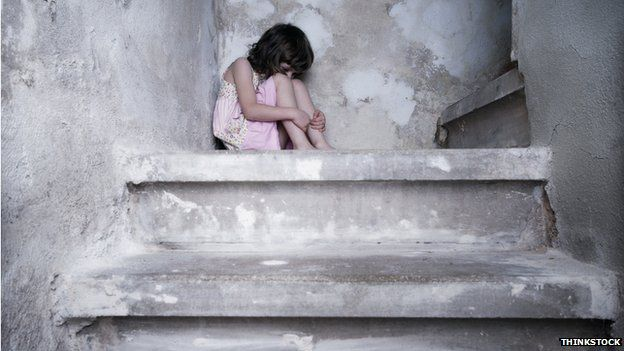 child curled up in a ball on stairs