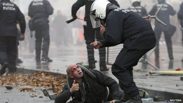 Riot police with injured protester in Brussels. 6 Oct 2014