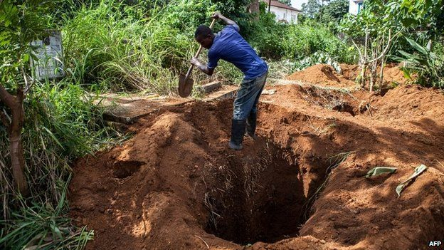 A funeral worker fills a grave after burying a body at a cemetery in Freetown - 10 October 2014