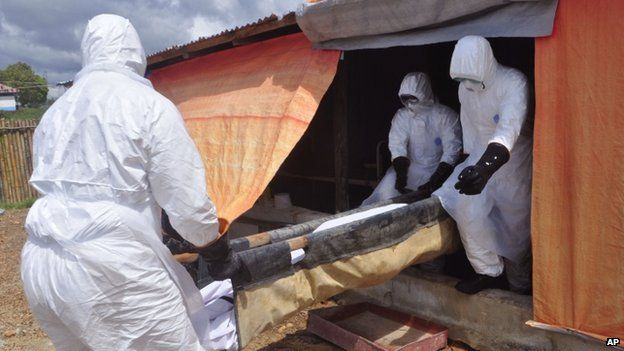 Ebola health care workers carry the body of a woman suspected of dying from the disease from a building used as a mortuary by the Bomi County Ebola Clinic on the outskirts of Monrovia, Liberia (7 November 2014)