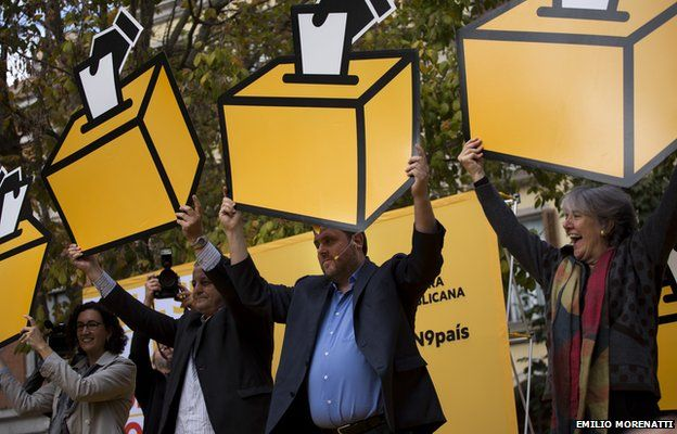 Oriol Junqueras, head of the pro-independence Republican Left of Catalonia, center, holds a drawing a of ballot box during a rally ahead of voting on an informal poll, scheduled for next Sunday, in Girona, Spain, on Saturday Nov.8, 2014