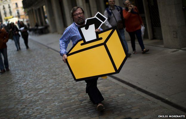 Businessman Emilio Busquets carries a drawing of a ballot box to decorate his shop ahead of voting on an informal poll, scheduled for next Sunday, in Girona, Spain, on Saturday Nov.8, 2014