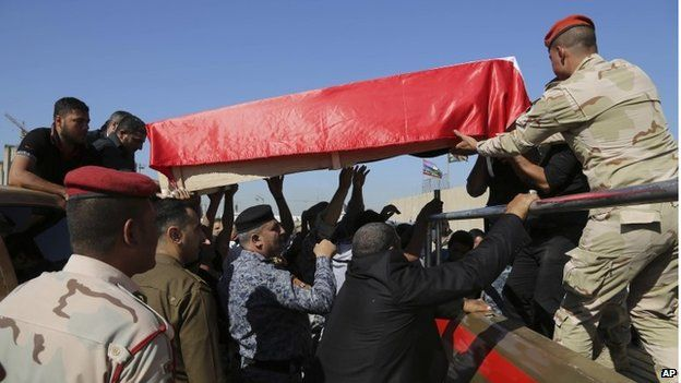 Mourners grieve as the body of police Lt. Gen. Faisal Malik is taken for burial before a funeral procession in Baghdad, Iraq, Saturday, Nov. 8, 2014