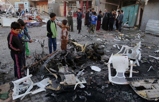 Civilians inspect the aftermath of a car bomb explosion in Sadr city, Baghdad, Iraq., Sunday, Nov. 9, 2014
