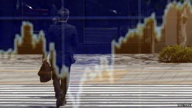 Man reflected in an electronic board outside a brokerage in Tokyo