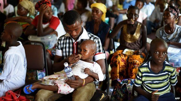 A child who survived the Ebola virus is fed by another survivor at a treatment centre in Hastings, on the outskirts of Freetown, on 11 November 2014.