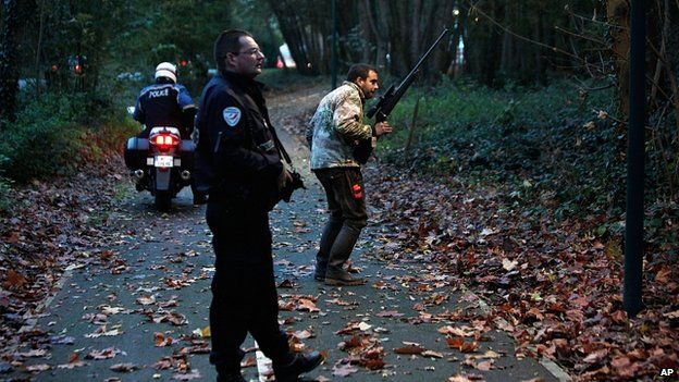 Police with tranquilizer gun walk through a wood in Montevrain, east of Paris. 13 Nov 2014