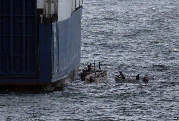 """Somali pirates in small boats are seen alongside the hijacked """"Faina"""""""