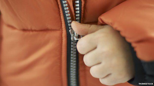 Child zipping up winter jacket