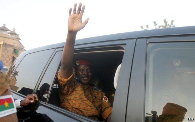 Burkina Faso's army-appointed leader, Lt Col Isaac Zida waves after the signature of a transition charter at the Masion du Peuple in Ouagadogou on 16 November 2014.