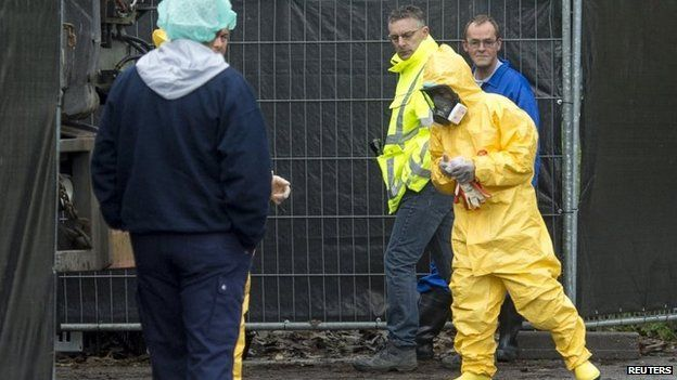 An expert wearing a protection suit arrives at a poultry farm, where a highly contagious strain of bird flu has been found, in Hekendorp, the Netherlands, 17 November 2014