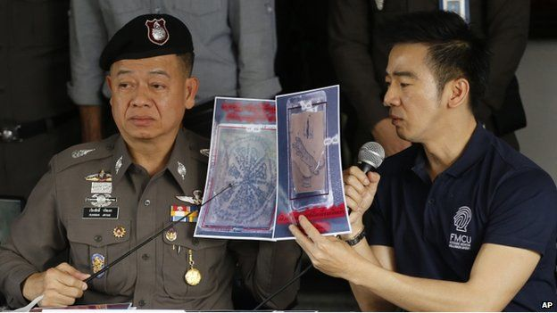 Thai police officers show pictures of a tattooed human skin during a press conference at Bangpongpang police station in Bangkok, Thailand, Monday, 17 Nov 2014
