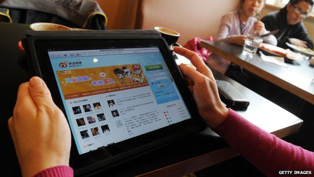 A woman views the Chinese social media website Weibo at a cafe in Beijing on 2 April, 2012