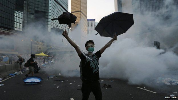A protester raises his umbrellas in front of tear gas which was fired by riot police to disperse protesters blocking the main street to the financial Central district outside the government headquarters in Hong Kong on 28 September, 2014