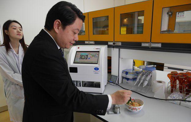 Video still of scientists testing a bowl of tom yum gung