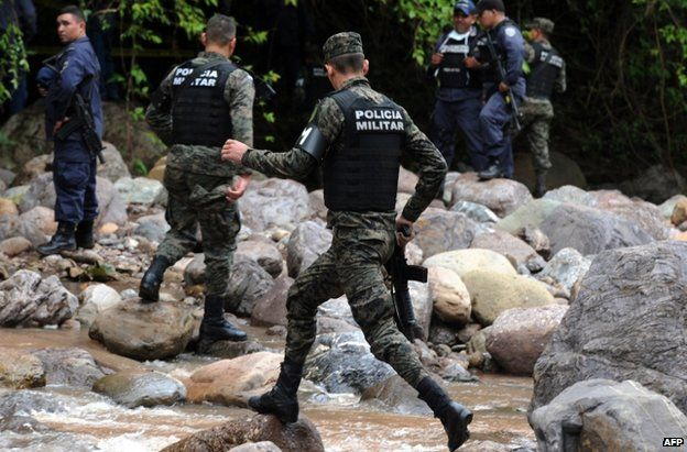 Police secure the area where the bodies were found by the River Aguagua, 19 November