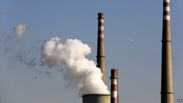 A passenger airliner and birds fly past a coal-fired power plant in Beijing, China - 13 November 2014