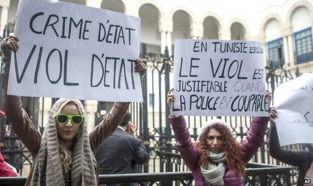 Tunisian women demonstrate outside a courthouse where three police officers face charges of raping of a 27-year-old woman, in Tunis, Tunisia, in March 2014