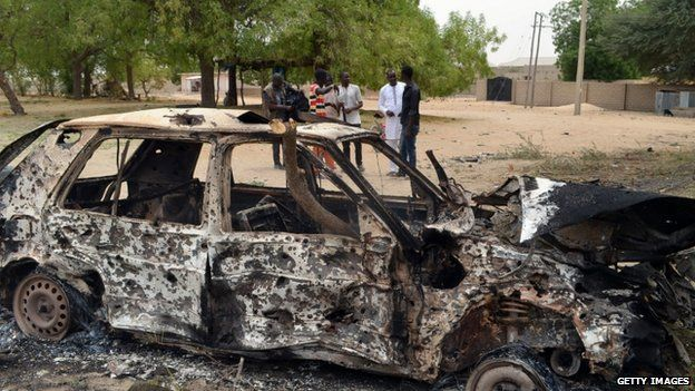 People stand by the wreckage of a car that has been blown up by suspected Boko Haram militants in Nigeria's troubled north-eastern city of Maiduguri on 25 March 2014