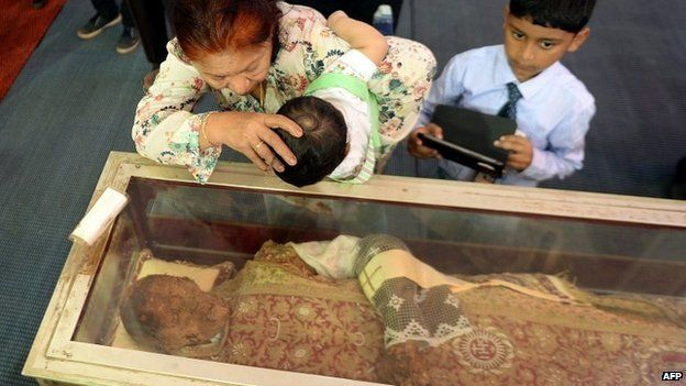 An Indian Christian helps a child to kiss the casket carrying the remains of Saint Francis Xavier in Goa - 22 November 2014