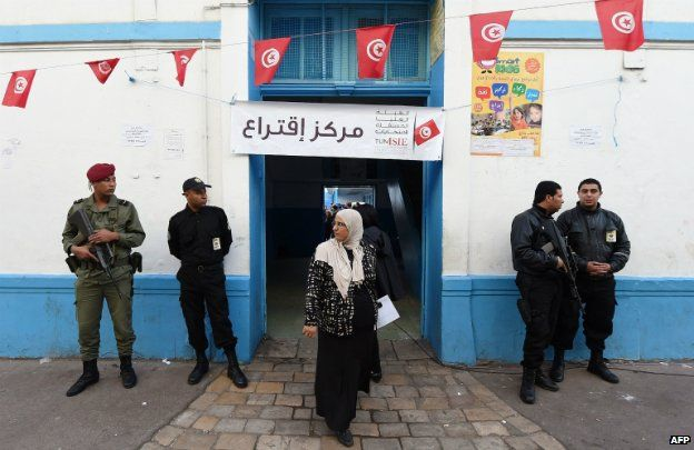 Tunisian security officers stand guard outside at a polling station in Tunis - 23 November 2014