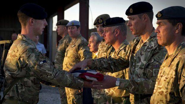 Signaller Jason Fleck presenting the Union Flag to Commander JFSp Brigadier Darrell Amison at Kandahar Air Base, Afghanistan