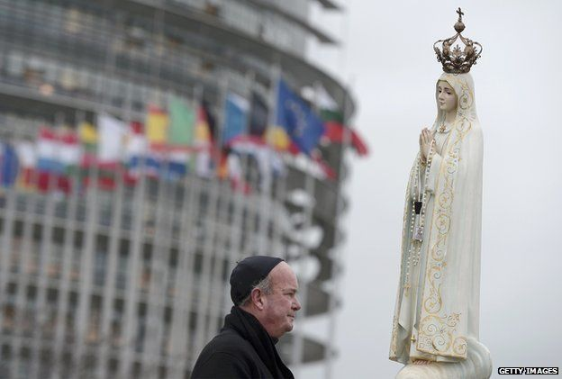 A cleric stands near a statue of the Virgin Mary in front the European Parliament building in Strasbourg, France, on 24 November 2014