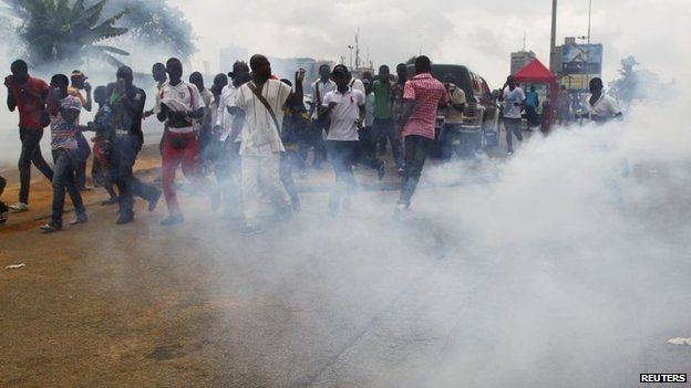 Demonstrators cover their faces from tear gas fired by security forces on November 25, 2014