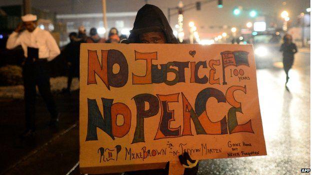 Demonstrators march along a street in Ferguson, Missouri, on November 26, 2014