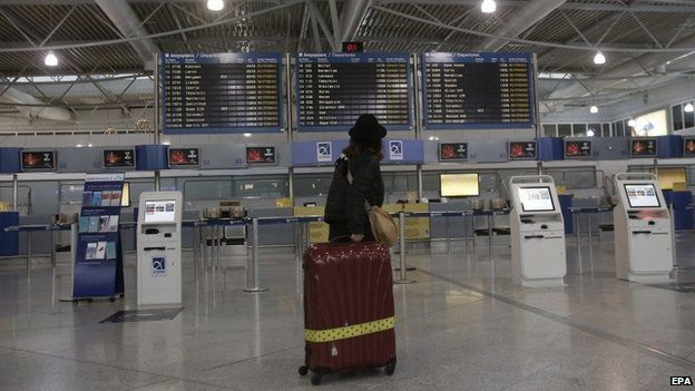 A commuter looks at a departure board during a strike in Greece