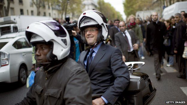 Francois Hollande rides on the back of a scooter while campaigning in Paris, 11 October 2011