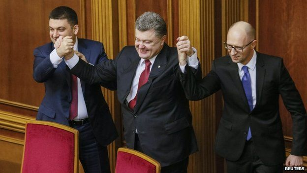 Ukraine's President Petro Poroshenko (centre) holds up the hands of newly appointed Prime Minister Arseny Yatsenyuk (right) and newly appointed parliamentary speaker Volodymyr Hroysman during a parliament session in Kiev