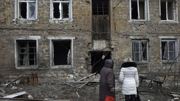 Women stand outside their house after government shelling in the eastern Ukraine city of Donetsk