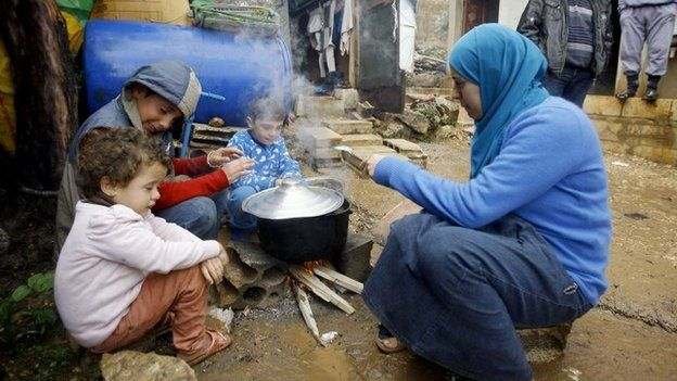 Syrian refugees prepare food near their tent at a camp in Lebanon's Chouf mountains (11 December 2013)