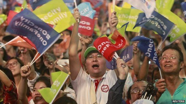 Supporters wave flags after Taipei's mayoral candidate Ko Wen-je won the local elections in Taiwan