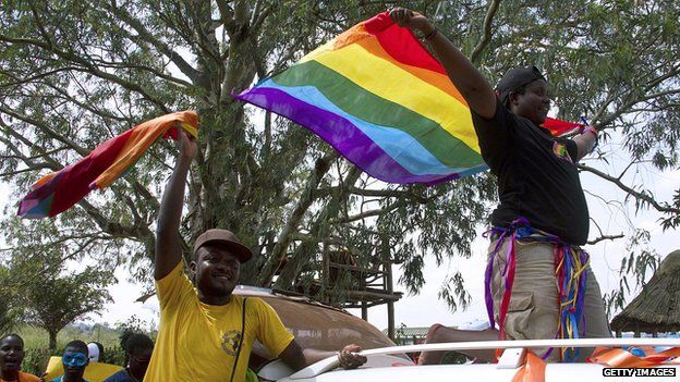 Ugandans wave a rainbow flag at a gay pride rally in Entebbe (file pic Aug 2014)