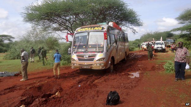 Kenyan security forces and others gather around the scene on an attack on a bus about 50km (31 miles) outside the town of Mandera, near the Somali border in north-eastern Kenya, Saturday, Nov. 22, 2014. (AP Photo)